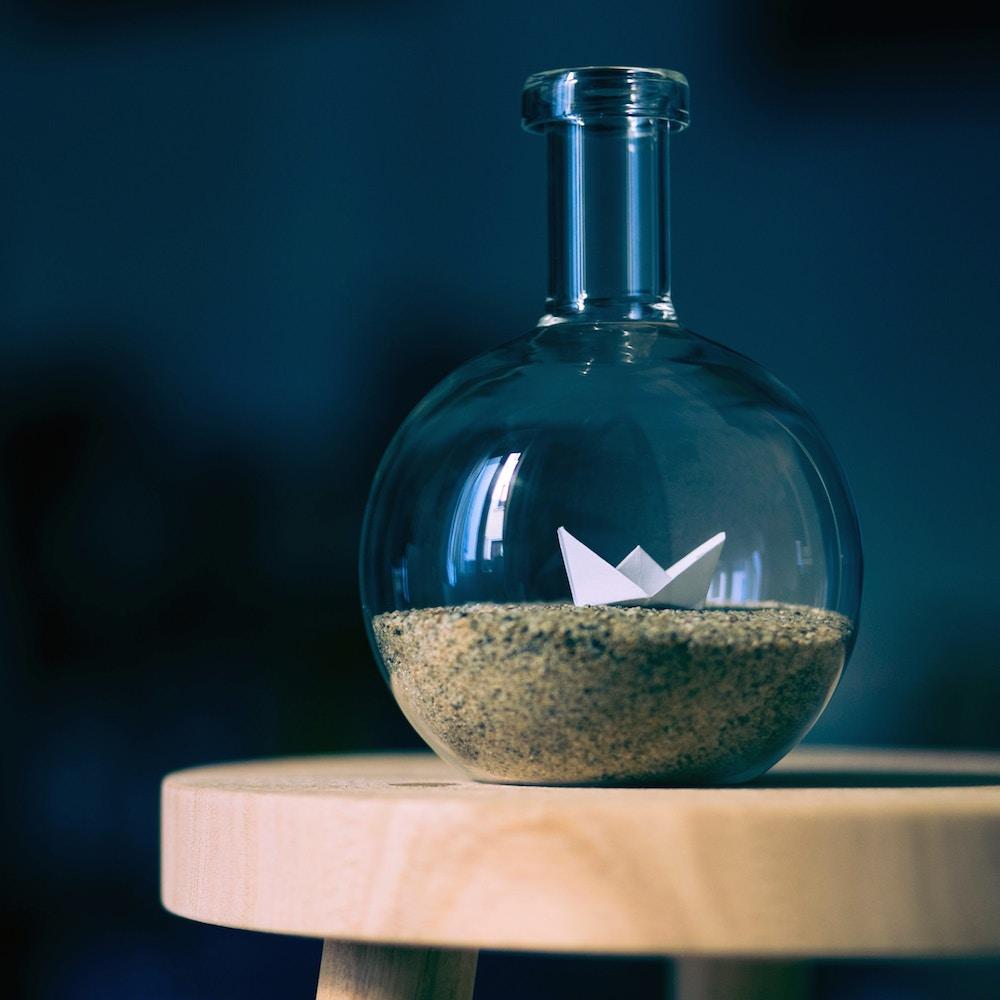 Vase mit Papierschiff